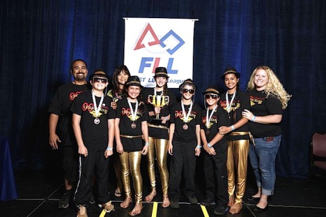 Kawika Gonzales and Jenn Whitted, coaches for the Molokai Golden Eyes robotics team, bracket the six-member team after it won the Champions Trophy at the FLL State Robotics Championship Saturday.